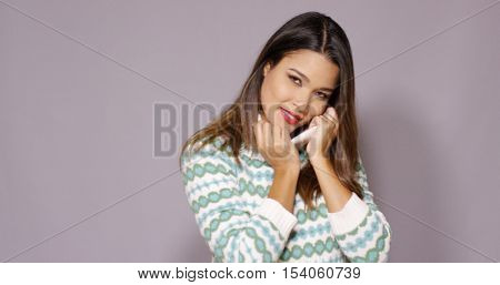 Pretty young woman snuggling into a woollen top