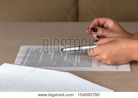 Divorce: hands of wife signing divorce documents and returning wedding ring