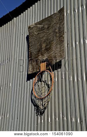 A basketball rim and hoop hang broken on a wooden backboard attached to a steel farm machine shed.
