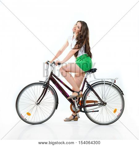 Fashion pretty woman with retro vintage bicycle over white background. Girl with bike in studio. Cheerful young woman riding her bike, summertime, isolated.