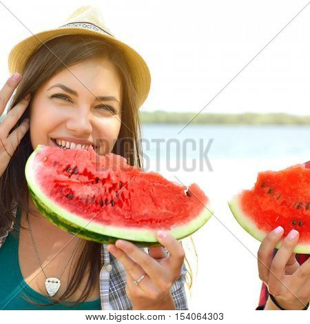 Happy young couple eating watermelon on the beach. Youth lifestyle. Happiness, joy, friendship, holiday, beach, summer concept. Group of young people having fun outdoor. Enjoy life, youth and summer.