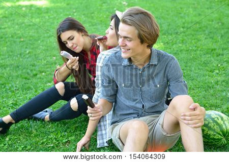 Young man and women eating chocolate ice-cream outdoor in summer park. Friends have fun outdoor. Leisure, youth, summertime.