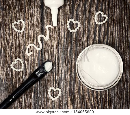 Favorite cosmetic products for skin around eyes. Eye cream squeezed out of tube, glass jar of light gel for eyelids and applying brush with sample and small hearts made of beads on wooden surface