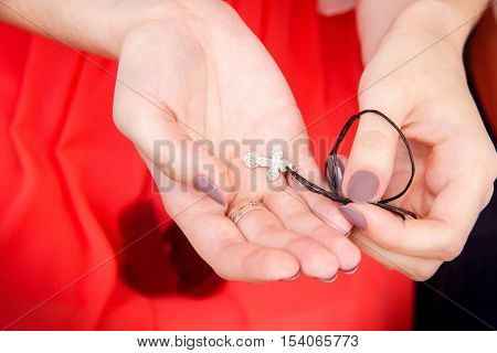 A girl in red dress holding in her hands a silver  for baptism.