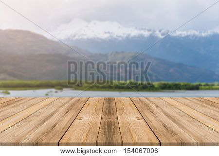 Wooden board empty table in front of blurred background. Perspective brown wood table over blur lake in forest mountain background - can be used mock up for display or montage your products.