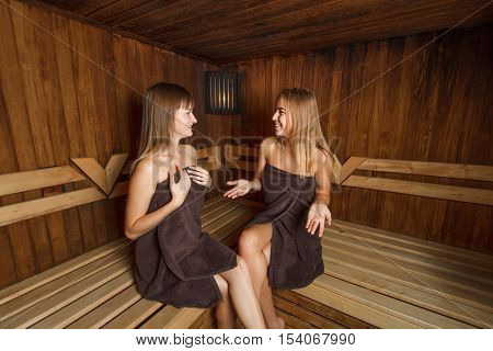 Two young girls in towels in sauna.