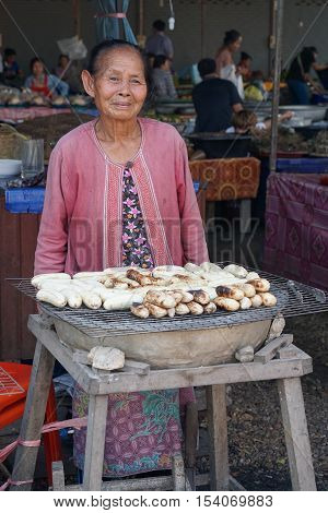 VIENTIANE, LAOS - FEBRUARY 19, 2016: Old woman selling grilled bananas on a market on February 19, 2016 in Vientiane, Laos, Asia