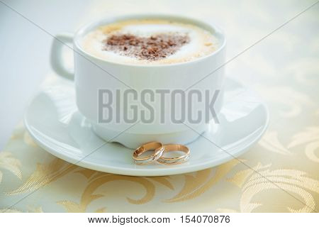 Wedding day. White cup of cappuccino with a painted heart of chocolate and a pair of gold wedding rings on a white saucer