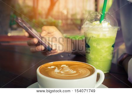 Woman use mobile phone and drink green tea frappe with coffee cup vintage tone.