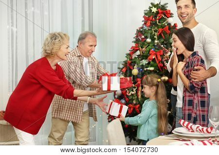 Happy members of family giving Christmas presents to each other