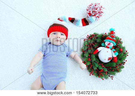 Cute baby lying on bedspread near Christmas wreath