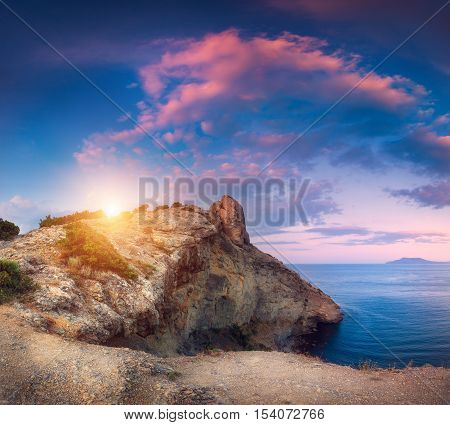 Mountain landscape with colorful blue sky with purple clouds sun and sea at sunset in Crimea. Twilight in mountains. Mountain path. Nature background. Beautiful vibrant panoramic landscape in dusk