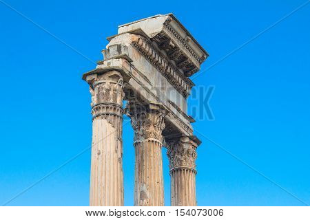 Ruins and columns of temple of Castor and Pollux in Roman Forum (Forum Romanum), blue sky in background, Rome, Italy