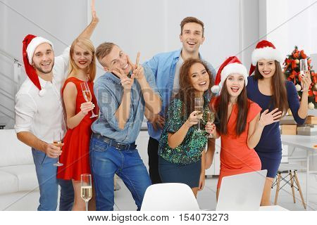 Young people with glasses of champagne celebrating Christmas at corporate party in office