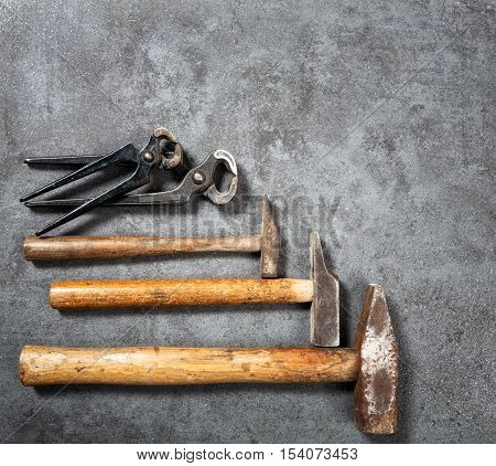 Tool background. Old vintage hammer and pincers collection on grunge stone workbench. Copy space. Top view flat lay