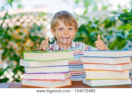 Adorable little kid boy with glasses and stack of colorful books. Cute happy preschool child and student is back to school and reading on warm day. Reading, books, education concept