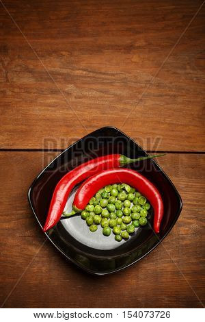 Red hot chilli peppers and crispy roasted green peas snacks coated in wasabi lying in ceramic black plate on brown wooden table. Copyspace. Top view.