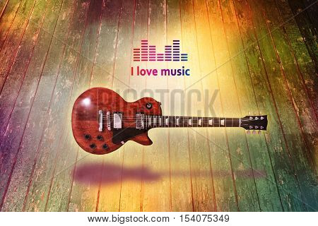 Creative art work concept. Electric guitar on rough wooden background. Text I LOVE MUSIC.
