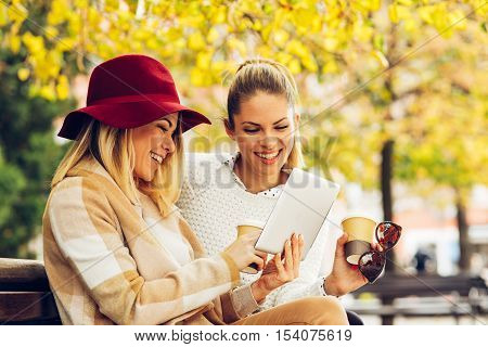 Two women using digital tablet on the bench in the city center