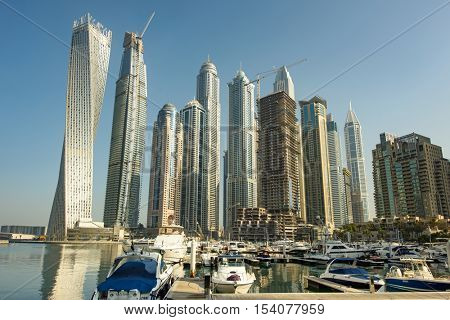 DUBAI, UAE - OCTOBER 09, 2016: Dubai Marina is a man made marina stretching over 3km of land. Surrounded by tall unique skyscrapers with apartments and restaurants, the marina is open to The Gulf.