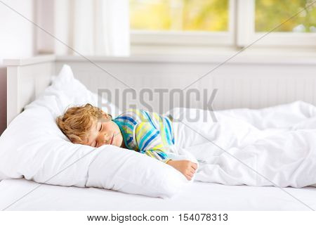 Carefree little kid boy sleeping in his white bed in colorful nightwear near big window with green and yellow autumn foliage. Funny happy child playing and smiling. Family, vacation, childhood concept