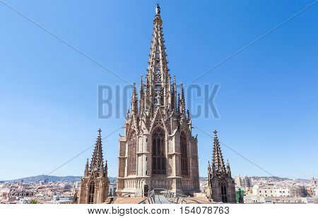 Cathedral of the Holy Cross and Saint Eulalia in Barcelona, Spain. On the roof. The upper part of the spire of the cathedral in the background of the city.