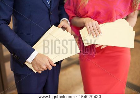 The man and the woman hold booklets in hand. The man and the woman hold invitation cards in hand. Envelopes in hands close up.