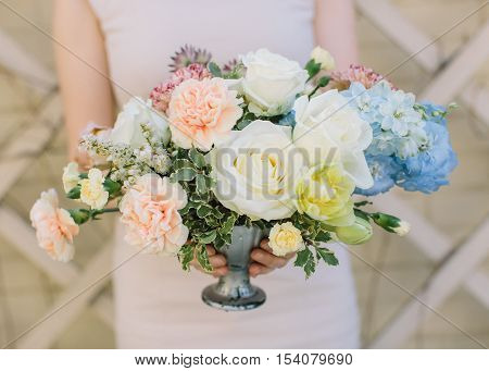 Wedding decor. Festive decor. Bouquet from spring flowers. Wedding bouquet. Girl holds a vase with the flowers. Pastel tone.