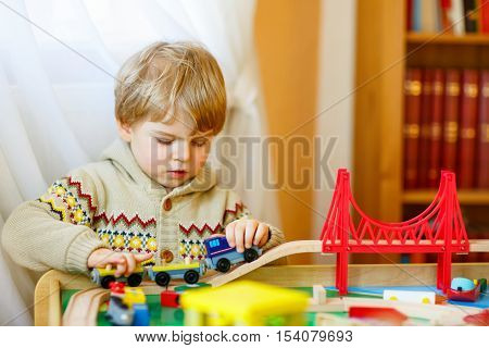 Little toddler boy playing with wooden railway, indoors. Blond funny kid child having fun with toys and learning. Creative leisure.