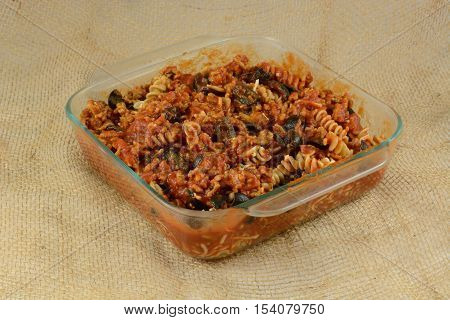 Casserole preparation of cooked whole wheat rotini pasta, ground turkey meat, sliced black olives and tomato sauce in glass baking dish