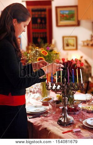 A woman prays before lighting candles for the Jewish holiday of Hanukkah.