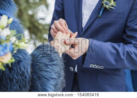 Close up groom put the wedding ring on bride, wedding in winter