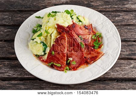 Sliced Gammon Steak with mashed potato on wooden background