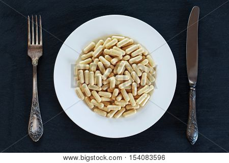 the medical pills in plate on a black background