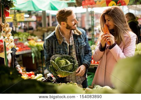 Loving couple buying vegetables at the market