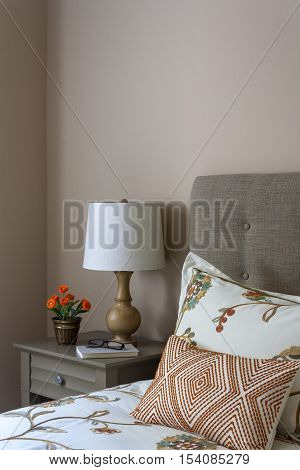 Bed with upholstered headboard and beside table with lamp book and flowers