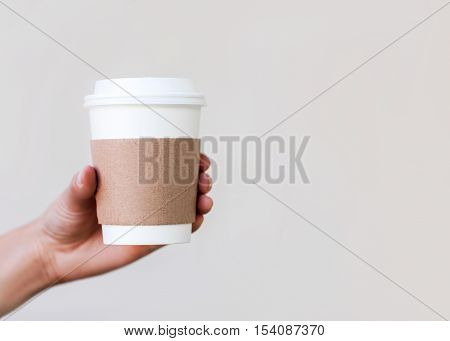 Paper cup of coffee to go in the hand