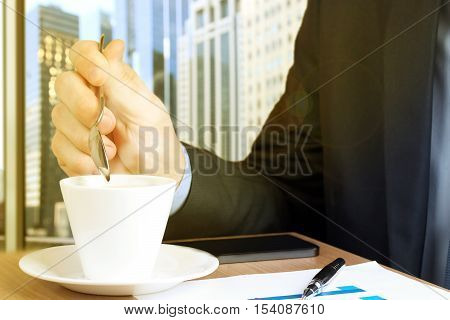 Businessman drinking coffee and using the mobile smart phone.