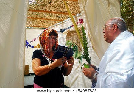 A Jewish man and a woman bless on the four species in the Sukkah in Sukkoth jewish holiday.