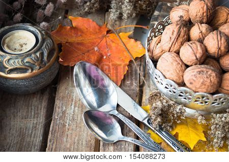 Silver plate with walnuts, candle, autumn leaves and spoons