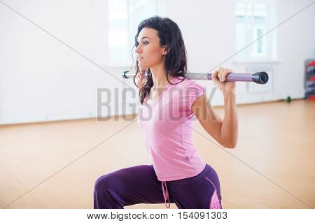 Fit woman exercising in fitness club doing lunge squats with barbell on her shoulders