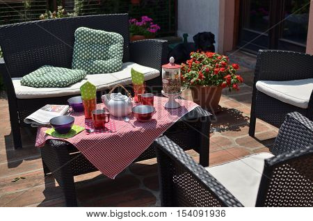 Set of garden furniture with served breakfast and with black dog behind it