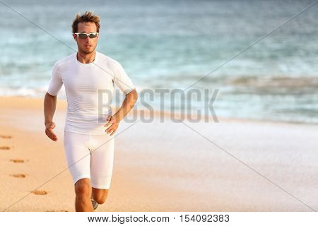 Sport athlete running on beach for triathlon race. Runner training cardio on beach race living an active and healthy lifestyle. Professional triathlete working out exercising at tropical ocean.