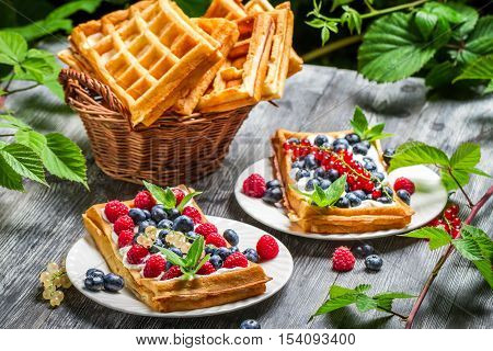 Fresh berry fruit on waffels on old wooden table