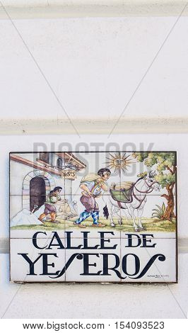 MADRID, SPAIN - MARCH 13, 2016: Closeup of the street sign. Street signs in Madrid are hand-painted ceramic tiles typically composed within 9 or 12 tiles. They depict the name of street and illustrations with special meanings.