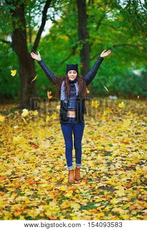 Young pretty long haired brunette throws up maple leaves and laughing in the autumn forest