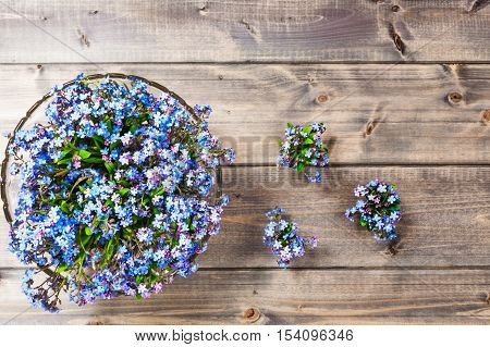 Flower on wooden background. Bowl of small blue forget me not flowers. Springtime. Copy space. Top view flat lay