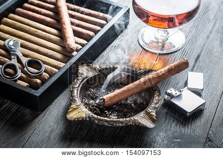 Taste of cognac and cigar fuming on old wooden table