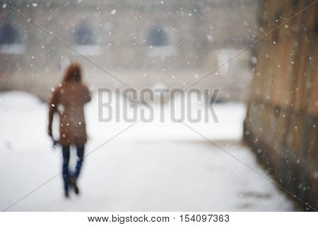 Blurred image of a man walking down the street back home after work during snowfall on a cold winter day.