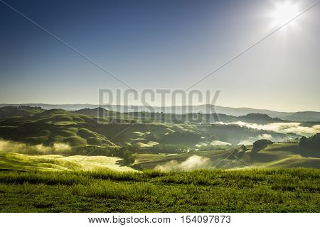 Misty hills in Tuscany at sunrise in summer